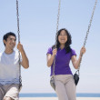 Asian couple swinging on swings — Stock Photo