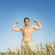 Pacific Islander man flexing in field — Stockfoto