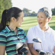 Asian mother and adult daughter holding golf bags — Stock Photo