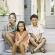 Hispanic siblings sitting on porch — Stock Photo