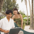 Stock Photo: Asicouple looking at laptop