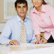 Multi-ethnic businesspeople next to blueprints — Stock Photo
