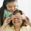 Hispanic girl covering mother's eyes — Stock Photo