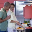 Stock Photo: AfricAmericcouple hugging in kitchen
