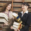 Multi-ethnic women carrying stacks of library reference books — Stock Photo