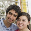 Multi-ethnic teenaged couple on carnival ride — Stock Photo
