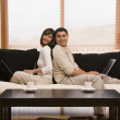 Hispanic couple sitting back to back on sofa — Стоковая фотография