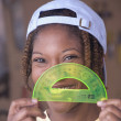 Stock Photo: AfricAmericwomwith protractor in front of face