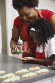 African mother and daughter decorating cookies — Stock Photo
