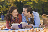 Hispanic couple reading on picnic blanket — Stock Photo