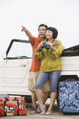 Asian couple with binoculars leaning on car — Stock Photo