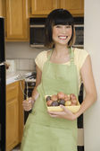 Asian woman holding bowl of potatoes — Stock Photo