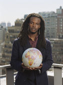 African man holding globe in urban scene — Stock Photo