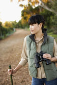 Asian woman holding binoculars — Stock Photo