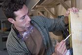 Hispánský muž měřící kus dřeva — Stock fotografie