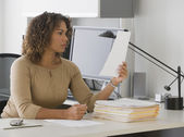 African businesswoman reading paperwork — Stock Photo