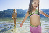 Asian sisters wading in lake — Stock Photo