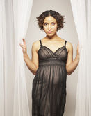 Pregnant Mixed Race woman standing in curtains — Stock Photo