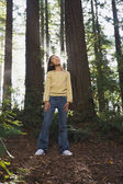 Asian girl standing in woods — Stock Photo