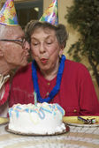 Senior woman blowing out birthday candle — Stock Photo
