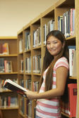Asian girl holding library book — Stock Photo