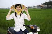 Asian woman sitting on motor scooter — Stock Photo