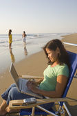 Asian woman typing on laptop at beach — Stock Photo