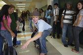 Teenaged boy riding skateboard in school hallway — Stock Photo