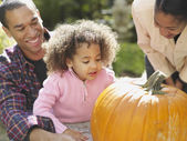 African family looking at pumpkin — Stock Photo