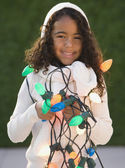 African girl holding Christmas lights — Stock Photo