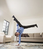 Hispanic businessman doing handstand in livingroom — Stock Photo