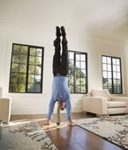 Hispanic businessman doing handstand — Stock Photo