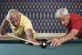 Multi-ethnic senior men aiming for same billiard ball — Stock Photo
