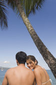 Asian couple sitting on beach — Stock Photo