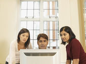 Multi-ethnic businesspeople looking computer — Stock Photo