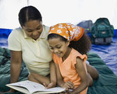 Mixed Race mother and daughter reading in tent — Stock Photo