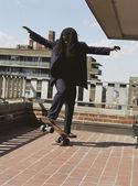 African man skateboarding on urban balcony — Stock Photo