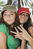 Hispanic teenaged girls making hand gestures — Stock Photo