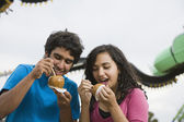 Multi-ethnic teenaged couple eating candied apples — Stock Photo