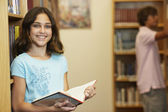 Girl holding library book — Stock fotografie