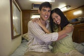 Multi-ethnic couple hugging on bed — Stock Photo