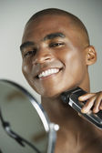 African man shaving with electric razor — Stock Photo