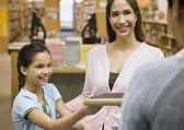 Mixed Race mother and daughter checking out library books — Stock Photo