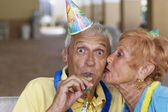 Senior woman kissing husband on birthday — Stok fotoğraf