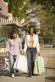 African teenaged girls carrying shopping bags — Stock Photo