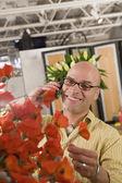 Hispanic male florist talking on telephone — Stock Photo