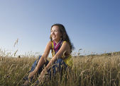 Hispanic woman sitting in field — Stock Photo