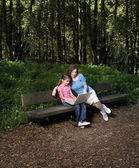 Hispanic mother and daughter looking at laptop in woods — Stock Photo