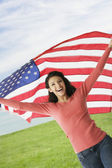 Hispanic teenaged girl holding American flag — Stock Photo