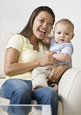 Asian mother hugging baby — Stock Photo